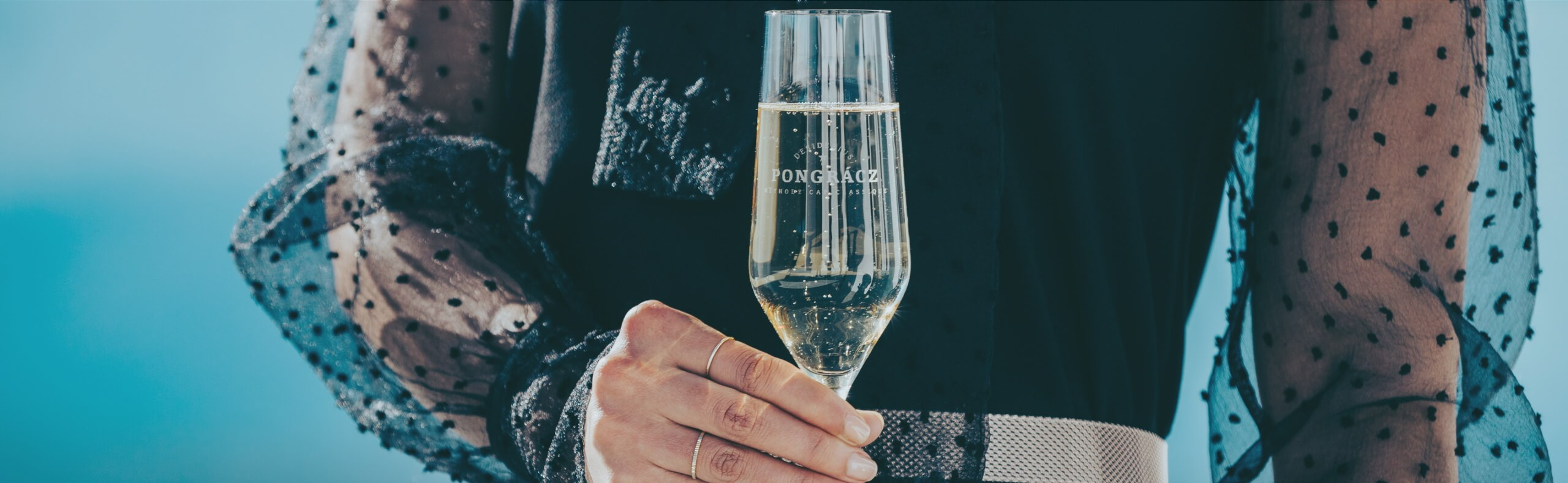 Lady holding a flute glass filled with Pongracz MCC