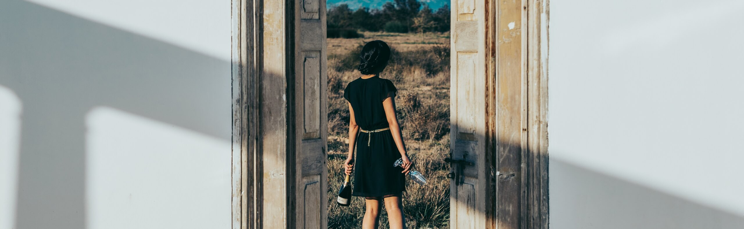 Young lady walking through wooded double-doors with Pongracz MCC and two glasses